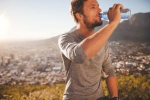 Homem bebendo água | Cálculos urinários e tratamentos por cirurgia robótica ou laparoscópica