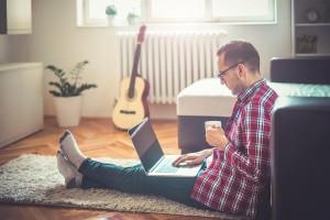 Homem segurando caneca e olhando notebook | Fatores que podem prejudicar a fertilidade masculina