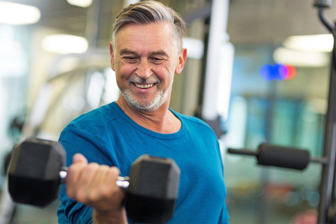 Homem grisalho levantando um haltere | O câncer de próstata atinge mais de 61 mil homens todos os anos no Brasil. Leia aqui as estatísticas, fatores de risco, prevenção e tratamento da doença.
