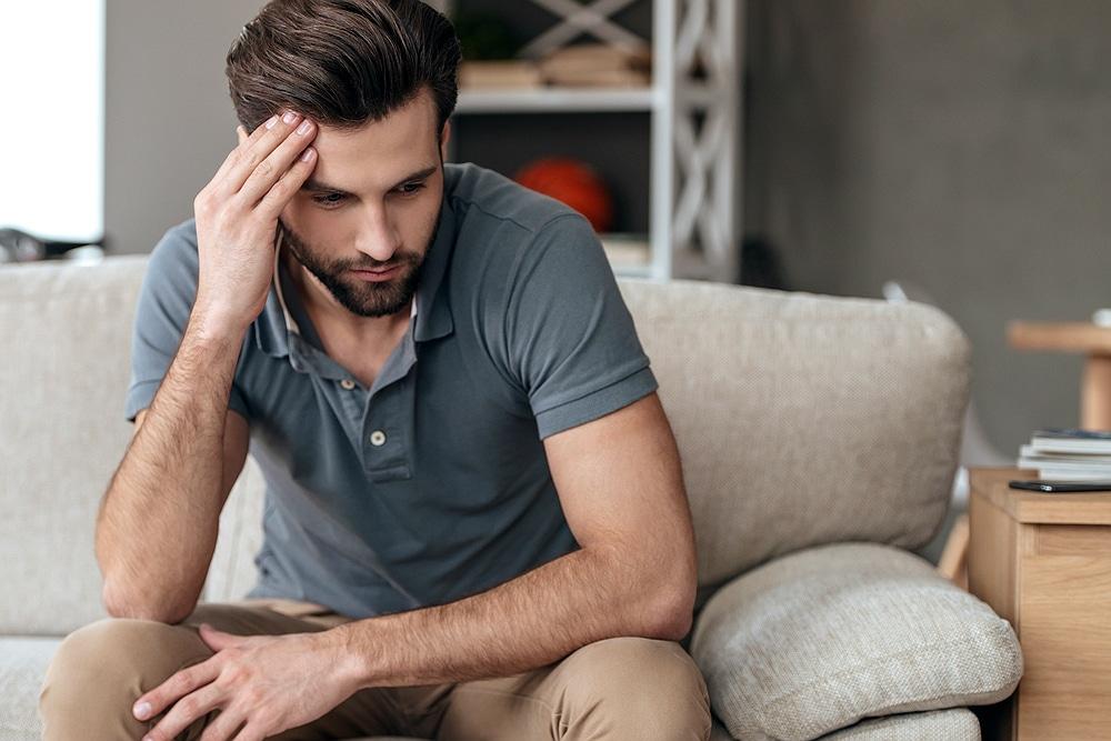 homem jovem sentado pensativo | Você sabe qual a relação entre as verrugas genitais e o HPV?