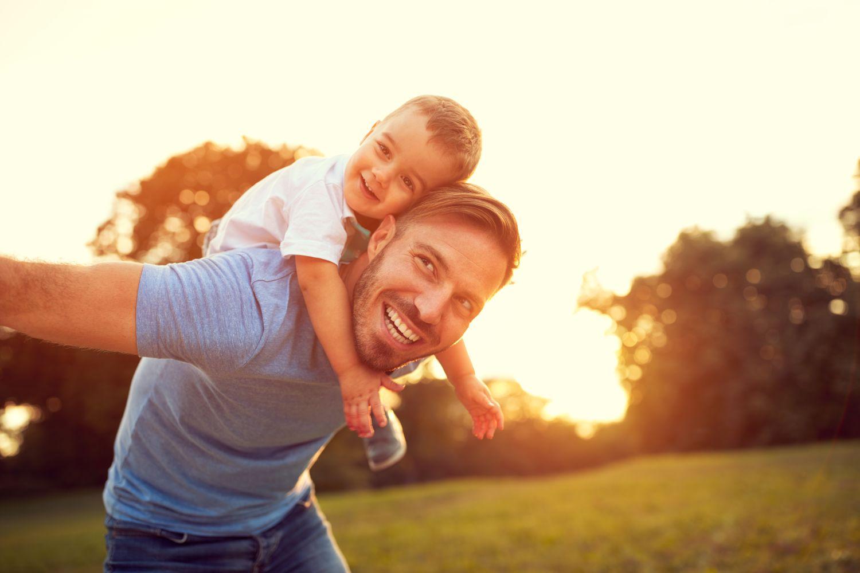 Homem sorrindo com o filho nas costas | Câncer de Próstata: é possível reduzir as minhas chances de ter?